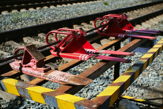 The red railway brake shoe lies on the rack.
