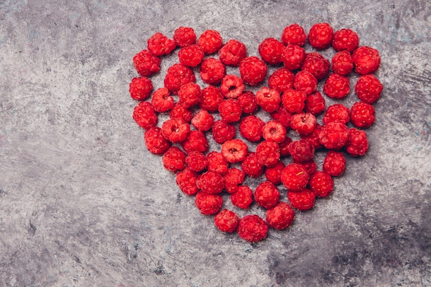 Red raspberries in a heart form on a gray table. top view.