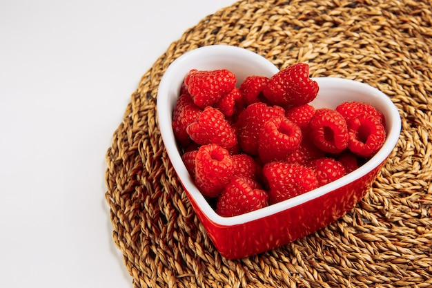 Red raspberries in a plate in the shape of heart high angle view on a wicker placemat and white background