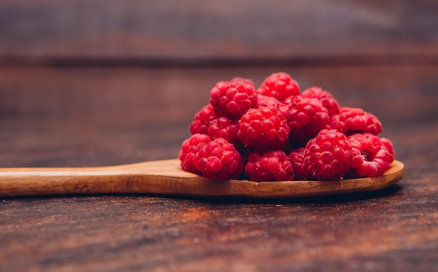 Red raspberries in a wooden spoon side view on a wooden table