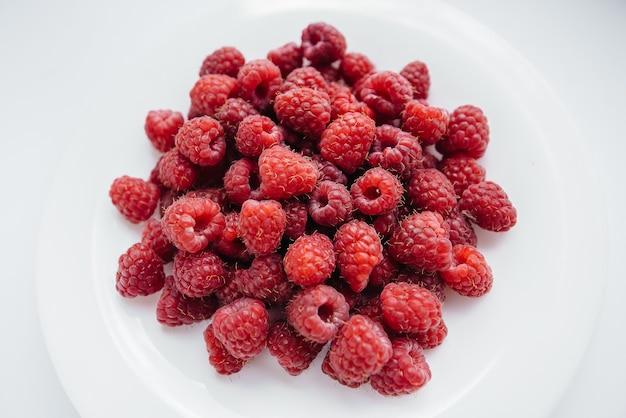 白い背景の上の赤いラズベリーベリーのクローズアップ。健康食品、天然ビタミン。新鮮なベリー。