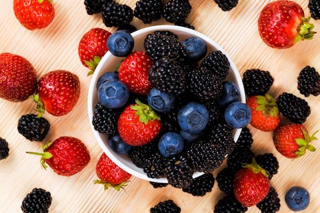 레드 라즈베리는 테이블에 블루 베리와 블랙 블랙 베리의 열매, 여름 시간, 잘 익은 맛있는 열매의 사진과 함께 거짓말을 닫습니다