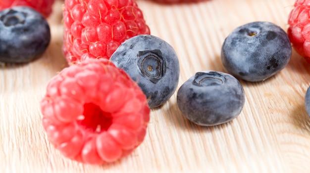 레드 라즈베리는 테이블에 블루 베리 열매와 거짓말, 여름철, 잘 익은 맛있는 열매의 사진을 닫습니다