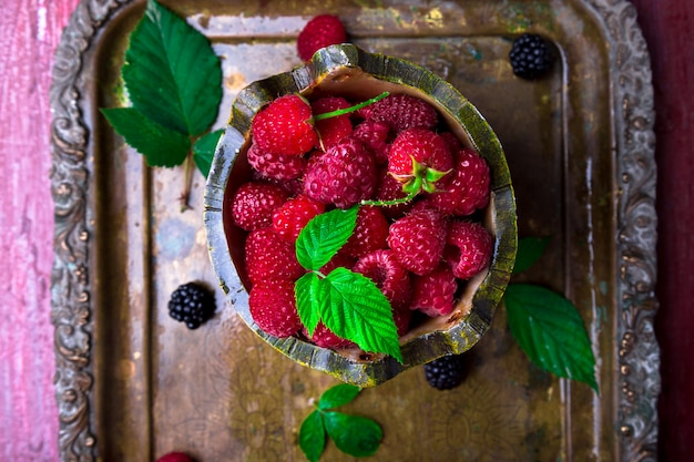 Red raspberry with leaf in a basket on vintage metal tray