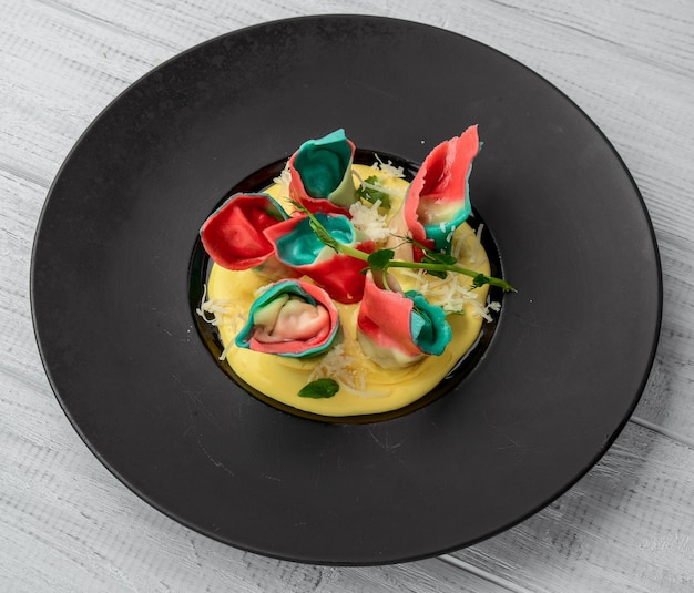 Red ravioli with mushrooms served on a black plate