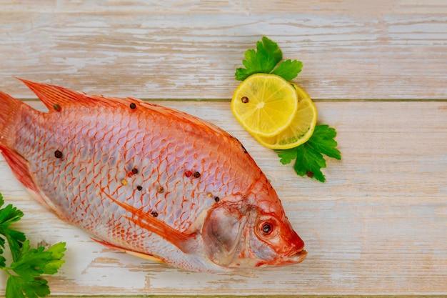 나무 테이블에 허브와 함께 붉은 원시 tilapia 물고기. 평면도.