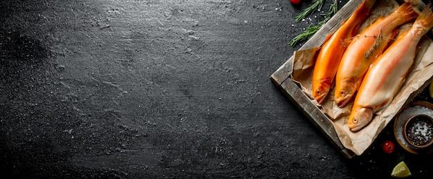 Красная сырая форель на подносе с бумагой, розмарином и специями на черном деревенском столе