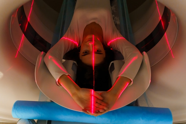 Red rays scan young girl on a ct scanner