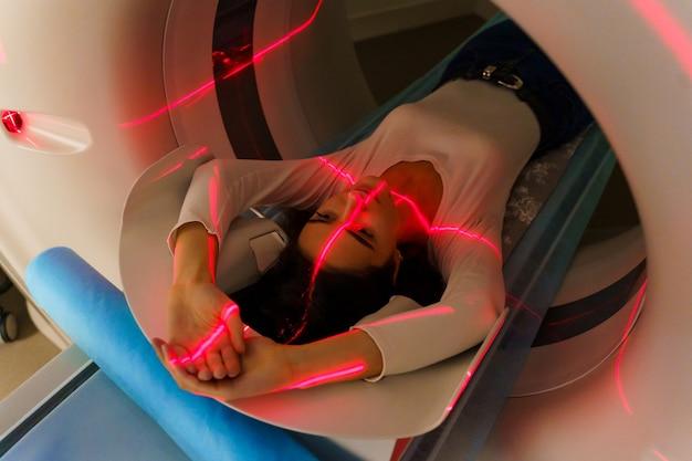 赤い光線はctスキャナーで若い女の子をスキャンします