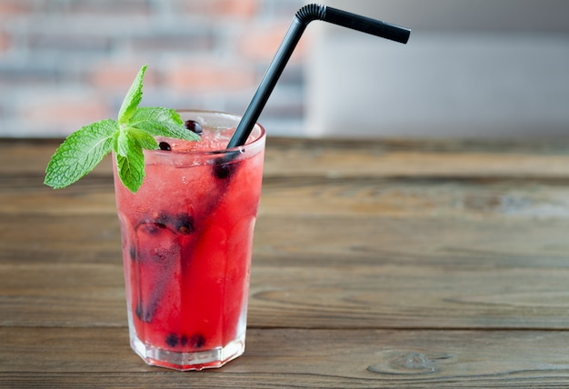 Red refreshing lemonade with berries and ice on a wooden table. summer drink.
