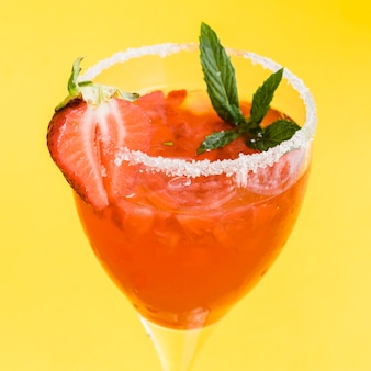 Red refreshing tasty cocktail with strawberry, mint, ice and sugar