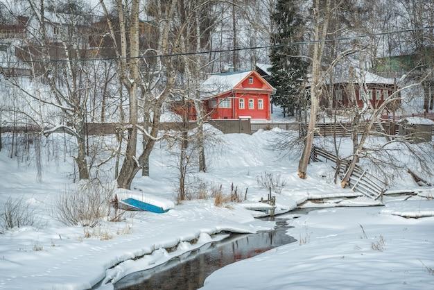 Красный жилой дом на берегу замерзшей реки шохонка в плёсе в свете зимнего дня под голубым небом