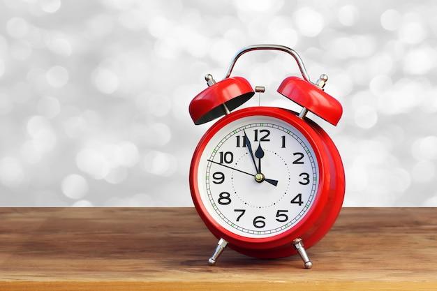 Красный ретро будильник в 12 часов на белом абстрактном bokeh. полночь, полдень. минуты до нового года. концепция празднования.