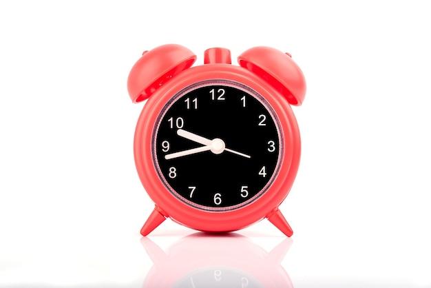 Red retro alarm clock isolated on white