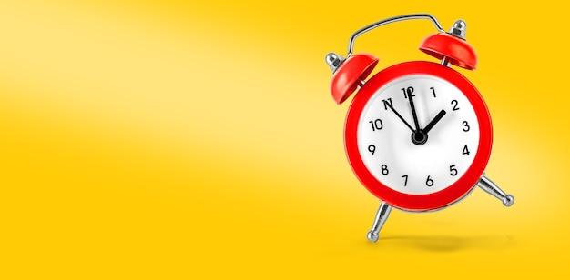 Red retro alarm clock isolated on yellow