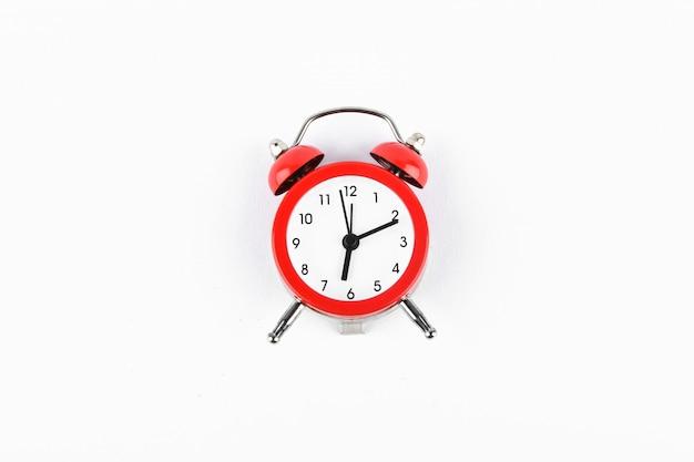 Красный ретро будильник на белом. круглый красный будильник на белом