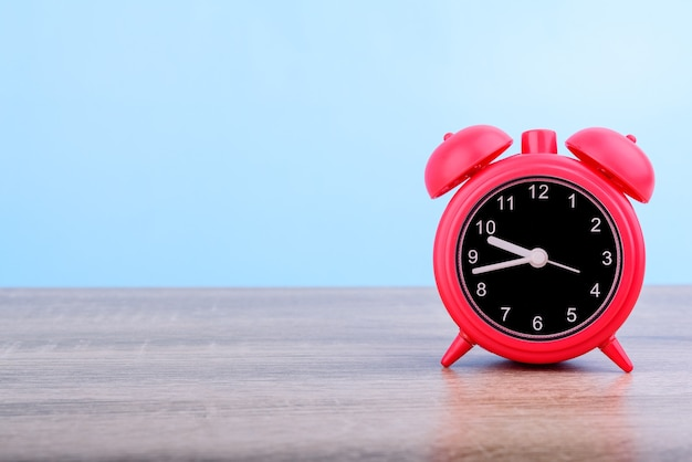 Red retro alarm clock put on wooden table isolated on blue background.