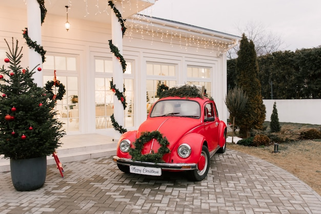 Red retro car decorated for christmas on the background of the white house.