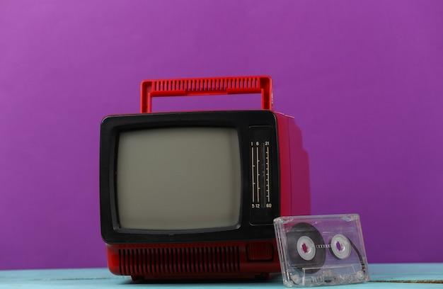 보라색 배경에 빨간색 복고풍의 오래된 휴대용 미니 tv 세트와 오디오 카세트.