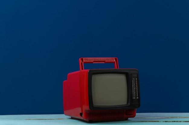Красный ретро старый портативный мини-телевизор на классическом синем фоне.