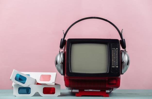 분홍색 배경에 헤드폰, 3d 안경이 있는 빨간색 복고풍 휴대용 미니 tv. 80년대, 레트로 스타일의 속성