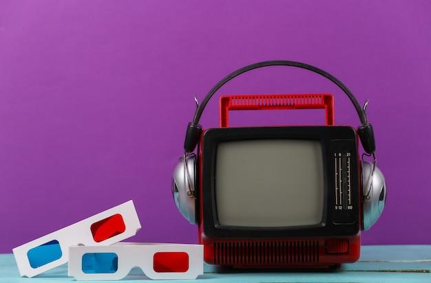 빨간색 복고형 휴대용 미니 tv에는 헤드폰, 보라색 배경에 3d 안경이 있습니다. 80년대, 레트로 스타일의 속성