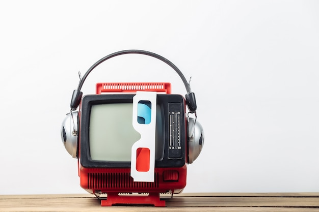 흰색 배경에 헤드폰, 3d 안경이 있는 빨간색 복고풍의 오래된 휴대용 미니 tv. 80년대, 레트로 스타일의 속성