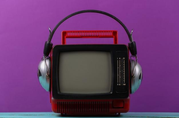 보라색 배경에 헤드폰이 달린 빨간색 복고풍의 오래된 휴대용 미니 tv.