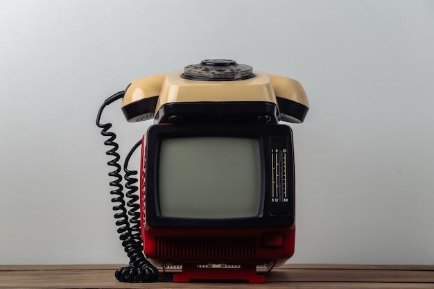 Красный ретро старый портативный мини-телевизор с поворотным телефоном на белом фоне.