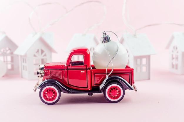 パステルピンクの背景にクリスマスの装飾ボールと赤いレトロなピックアップ。