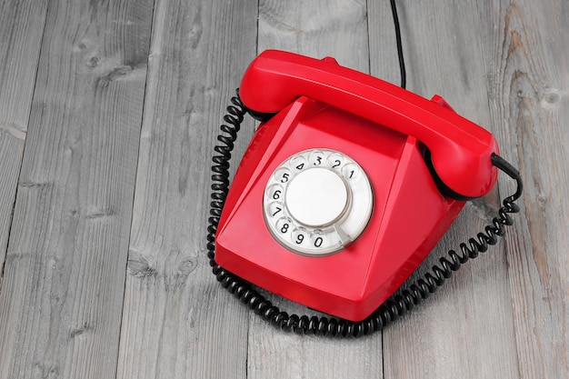 Red retro rotary phone on a wooden platform, top view.