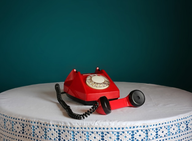 Red retro rotary telephone on a round table.