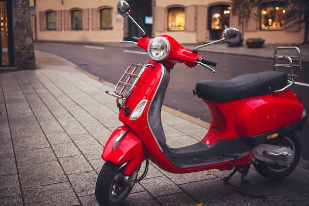 Красный ретро-скутер, старомодный мотоцикл, припаркован на тротуаре в городе.