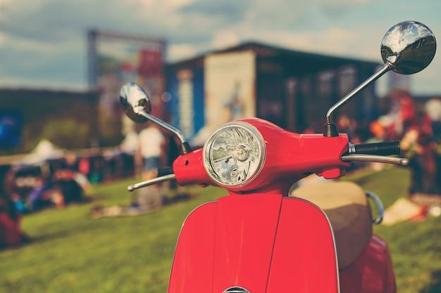 Красный ретро скутер на траве