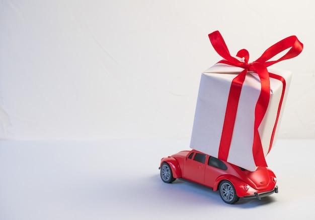 Red retro toy car delivering christmas or new year gifts on the roof on a white background.