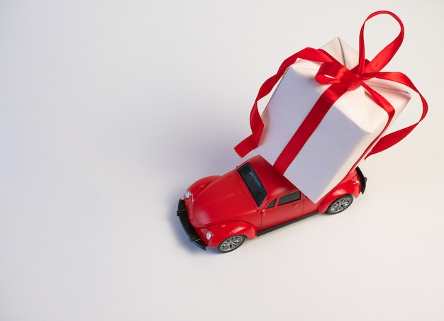Red retro toy car delivering christmas or new year gifts on the roof on a white background