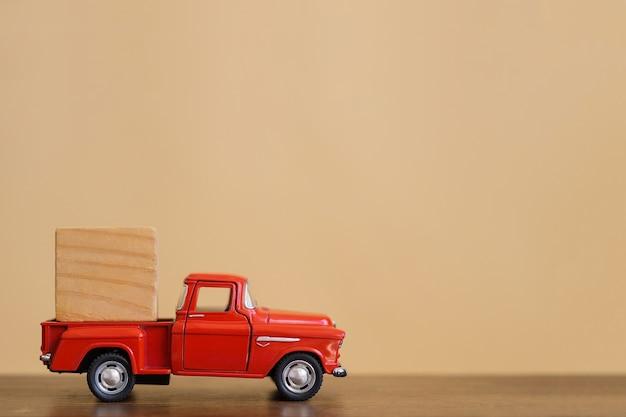 뒤에있는 나무 큐브를 가진 빨간 복고풍 장난감 트럭.