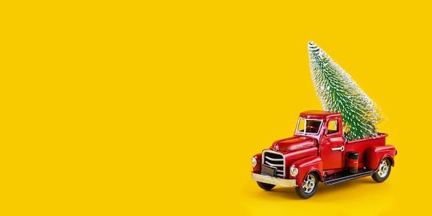노란색 배경에 트럭 본체에 크리스마스 트리가 있는 빨간색 복고풍 장난감 트럭. 배달, 크리스마스, 새 해 개념입니다. 크리스마스 트리 복사 공간 빈티지 장난감 모델 자동차입니다. 긴 와이드 배너