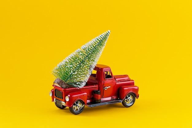 노란색 배경에 트럭 본체에 크리스마스 트리가 있는 빨간색 복고풍 장난감 트럭. 배달, 크리스마스, 새 해 개념입니다. 크리스마스 트리 복사 공간 빈티지 장난감 모델 자동차