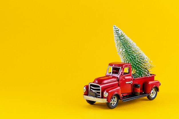 노란색 벽에 트럭 바디에 크리스마스 트리와 빨간 복고풍 장난감 트럭. 배달, 크리스마스, 새 해 개념. 크리스마스 트리 복사 공간 빈티지 장난감 모델 자동차.