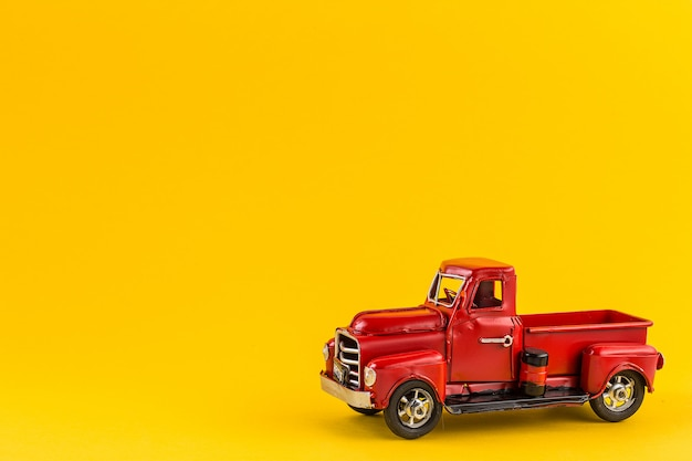 Red retro toy truck on yellow background.