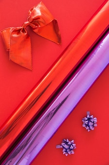 Red ribbon and purple bows with rolled up glitter paper on bright background