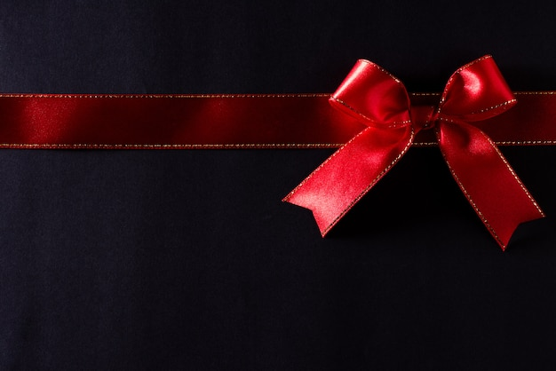 Red ribbon on black background with copyspace for text. black friday.