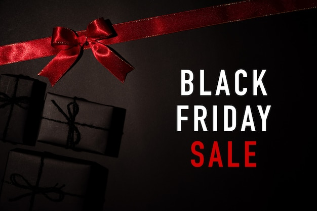 Red ribbon and black gift box on black background, black friday
