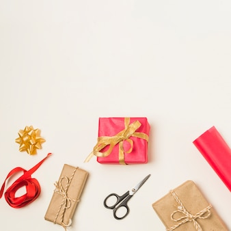 Red ribbon; bow; scissor and wrapping paper roll with wrapped gift boxes isolated in white background