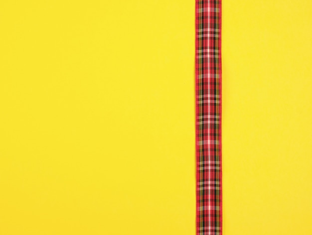 Red ribbon in the box on a yellow background