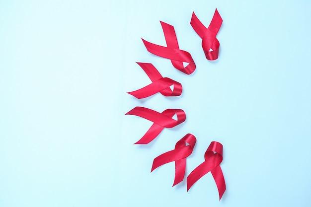 파란색 배경에 격리된 hiv 바이러스에 대한 에이즈의 상징으로 구성된 빨간 리본