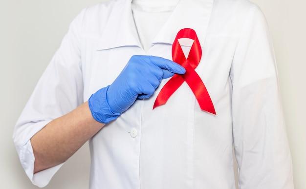 エイズとhiv世界の日のサポートのための赤いリボン、クローズアップ。女医の手。