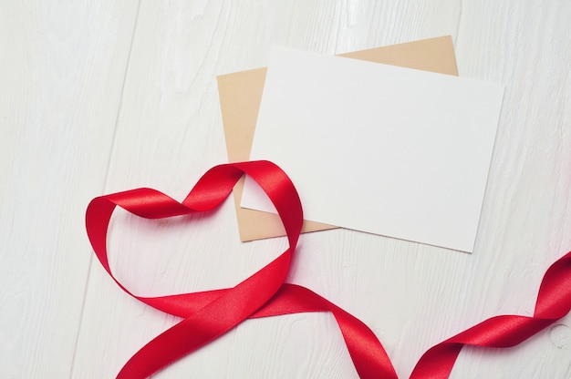 Red ribbon in form of heart and blank greeting card sheet of paper