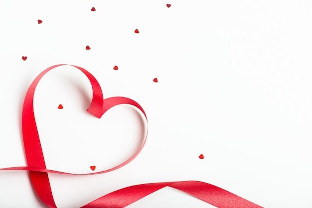 Red ribbon in the form of a heart with small shiny hearts on a white